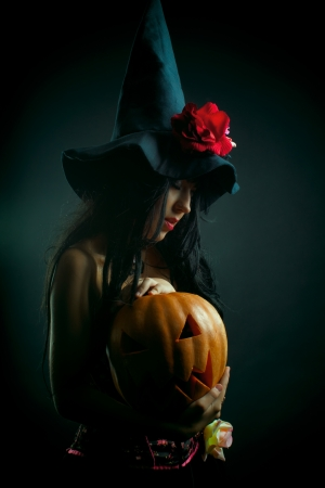 ove: Pretty witch with pumpkin posing ove dark background