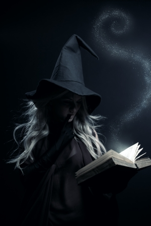 Young witch with magic book posing over dark background