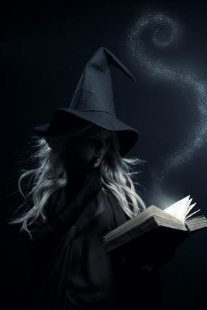 Bruja joven con el libro mágico posando sobre fondo oscuro
