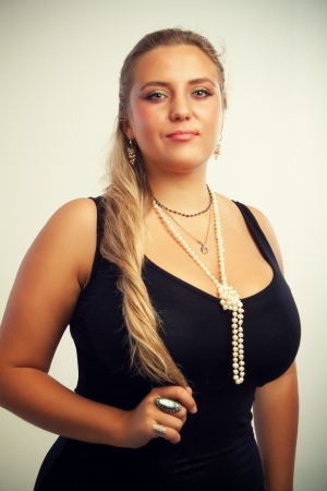 Young luxurious woman in black dress posing over white background