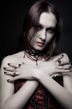 Portrait of pretty vampire in red corset posing over dark background photo