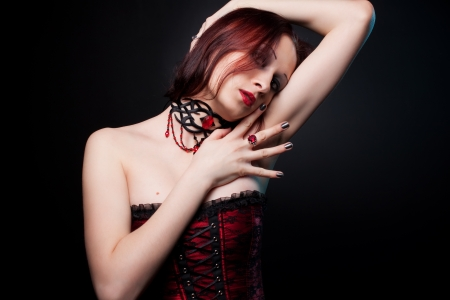 red corset: Seductive young girl in red corset posing over dark background