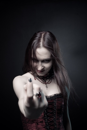 Seductive vampire in red corset posing over dark background