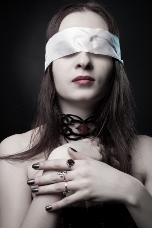 Portrait of pretty gothic girl with bondage on her eyes posing over dark background Stock Photo
