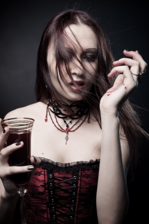 Portrait of pretty gothic girl with glass full of blood posing over dark background photo
