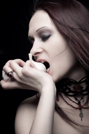 Pretty seductive vampire girl eating a garlic photo