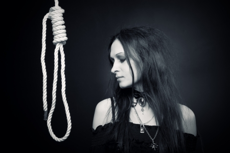sacrificio: Bastante triste g�tico chica posando sobre fondo oscuro Foto de archivo