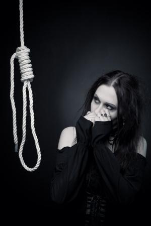gallow: Pretty gothic girl in black posing over dark background