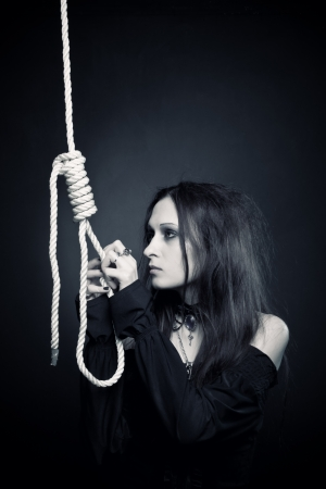 culprit: Pretty gothic girl in black clothes posing with gallows over dark background