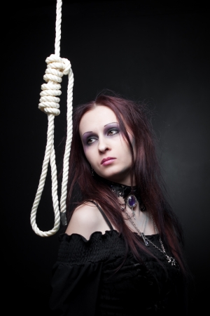 gallow: Pretty gothic girl posing with gallows over dark background