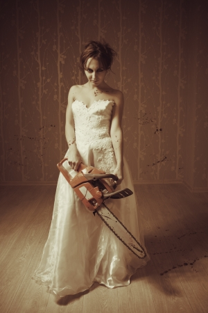 Pretty mad bride with bloody chainsaw in empty rooom photo