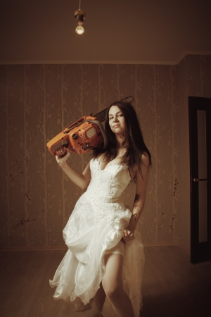 Pretty sexy bride with bloody chainsaw in empty room photo