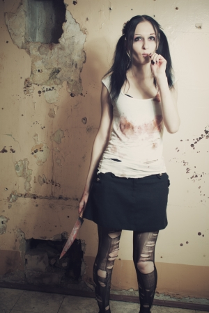 Pretty cute gothic girl with bloody knife and lollipop photo