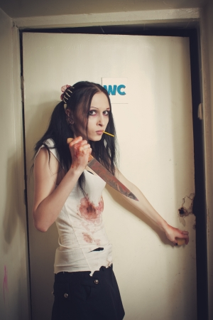 Portrait of seductive cute maniac girl with bloody knife photo