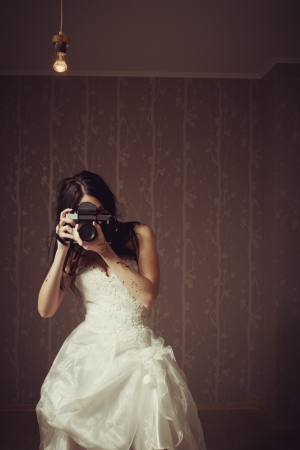 pretty seductive girl with old camera posing in the empty room photo