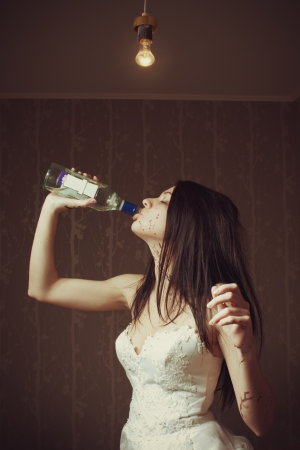 debauch: Pretty sexy bride drinking rum in the empty room