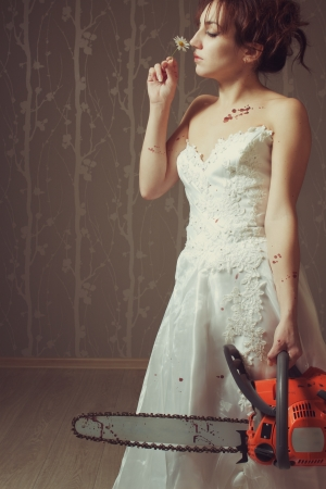 Pretty bride with bloody chainsaw smelling a chamomile in the empty room photo