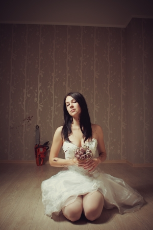 Pretty sexy bride sitting with flowers on the floor in the empty vintage room photo