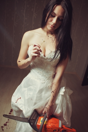Sexy bloody bride with chainsaw and chamomile in empty room photo