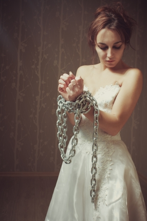 female prisoner: POrtrait of pretty young bride bounded by chains