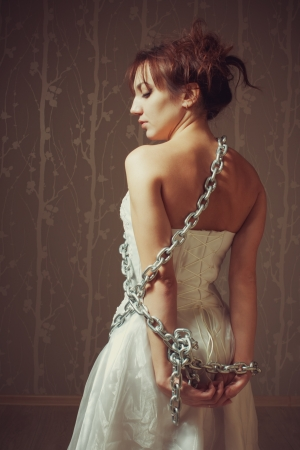 female sexy chains: Portrait of pretty young bride bounded by chains Stock Photo