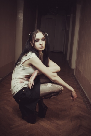 Seductive gothic girl sitting on the floor with bloody knife Stock Photo - 16662613