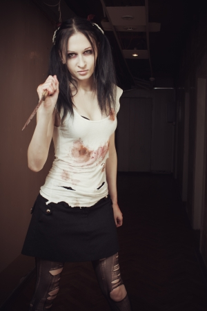 Seductive maniac girl with bloody knife photo