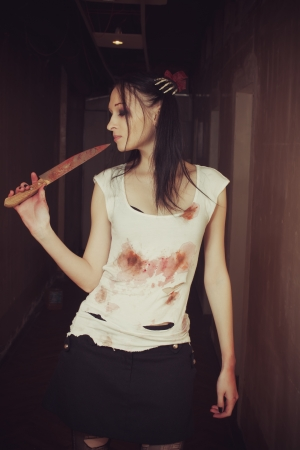 Pretty seductive gothic girl with bloody knife photo