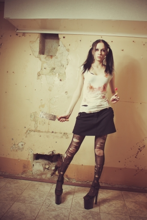 Seductive gothic girl with bloody chopper. Indoors shooting. Stock Photo - 16681384