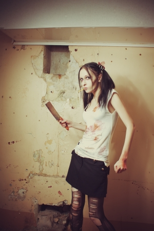 Seductive maniac gothic girl with bloody chopper. Indoors shooting. Stock Photo - 16681381