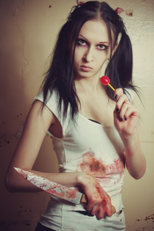 Pretty seductive gothic girl with bloody knife and lollipop photo