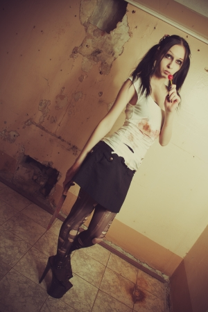 Pretty gothic seductive girl with bloody knife and lollipop photo