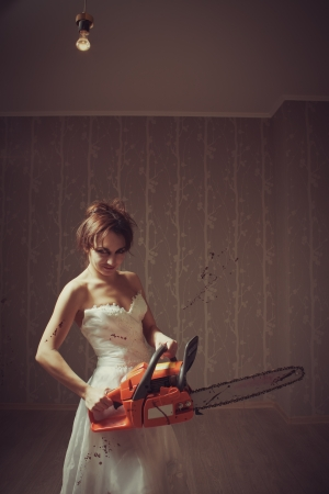Mad pretty bloody bride with chainsaw  Indoors shooting Stock Photo - 16715490