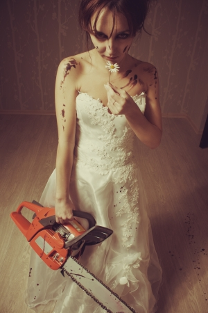 Pretty young bride standing in the empty room with bloody chainsaw and chamomile photo