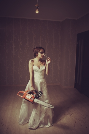 Pretty young bride with bloody chainsaw and chamomile photo
