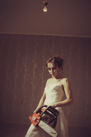 Young bride with bloody chainsaw  Indoors shooting  photo