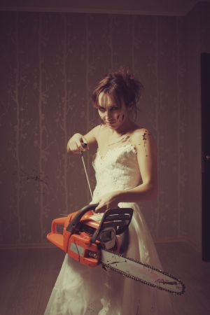 Crazy bloody bride with chainsaw  Indoors shooting  photo