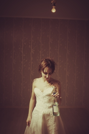 debauch: Young bride with bottle of vermouth  Indoors shooting