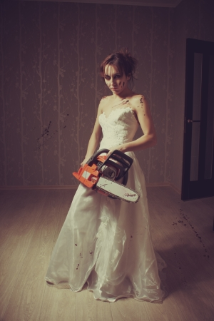 Mad young bride with bloody chainsaw in the empty room Stock Photo - 16859067