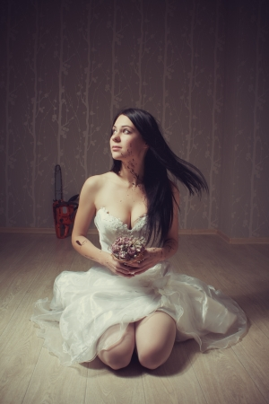 Pretty seductive bride with flowers sitting on the floor in the empty room. Stock Photo