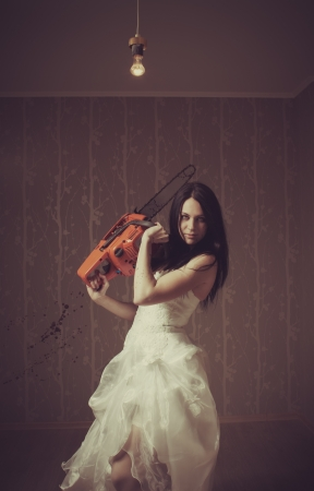 Pretty seductive bride with chainsaw  Indoors shooting Stock Photo - 16830198