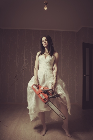 Seductive bloody bride with chainsaw  Indoors shooting
