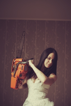 Seductive bride with bloody chainsaw  Indoors shooting  photo