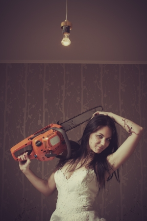 Seductive bride with bloody chainsaw  Indoors shooting Stock Photo - 16879898