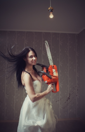 Seductive young bride with bloody chainsaw  Indoors shooting   Stock Photo - 16880455