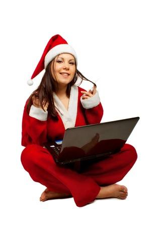 Funny smiling Santa helper with laptop isolated over white background. photo