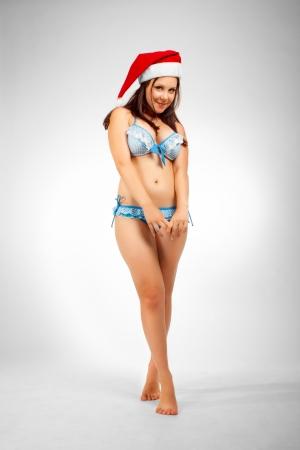 Pretty seductive Santa helper in bikini posing over white background. photo