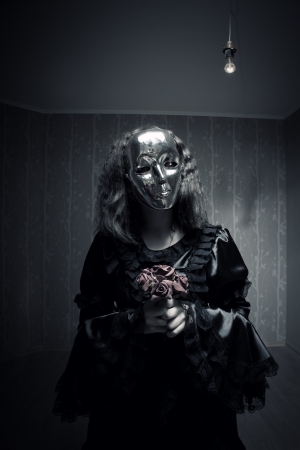Girl with flowers in mask standing in empty room photo