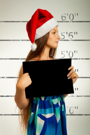 Mugshot of pretty Santa helper in red hat photo