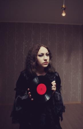 Sad gothic girl with vinyl  music plate photo